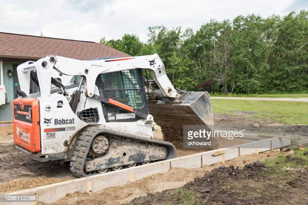Bobcat Dumping Sand lnside Concrete Forms