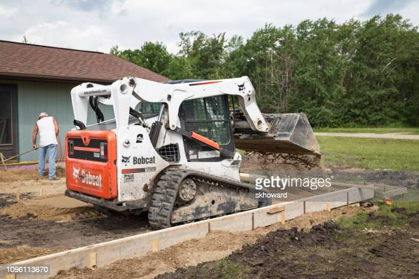 bobcat dumping sand lnside concrete forms - bobcat stock pictures, royalty-free photos & images