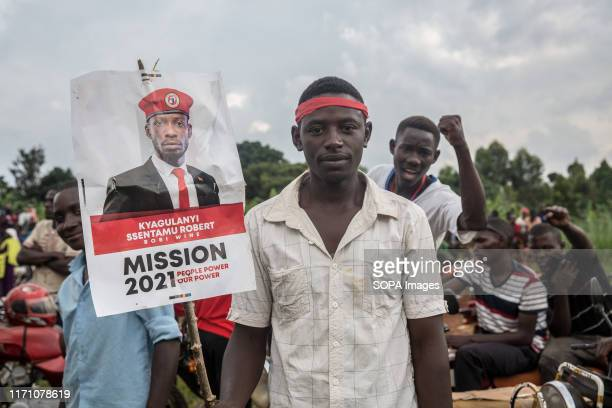 "Bobi Wine and ""people power"" opposition supporter, holds a placard during a rally in Hoima. Wine aka Robert Kyagulanyi, campaigned in Hoima ahead of..."