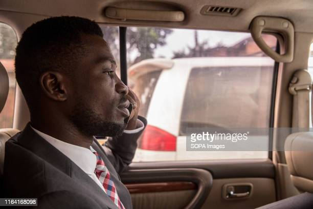 Bobi Wine talks on the phone while driving through Kampala at the beginning of a day of campaigning Bobi Wine whose real name is Robert Kyagulanyi a...