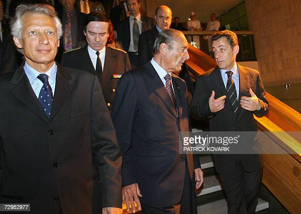 French President Jacques Chirac confers with Interior Minister Nicolas Sarkozy as he leaves the prefecture with French Prime Minister Dominique de...