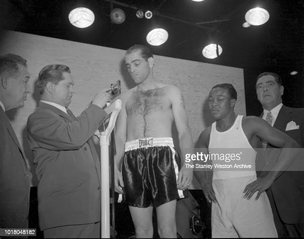 Bobo Olson weighs in before his bout as Kid Gavilan looks on in Chicago Stadium Chicago Illinois April 2 1954 Bobo Olson goes on to be declared the...