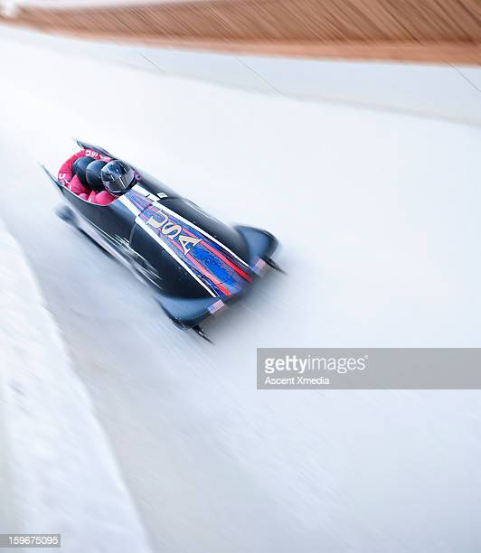 Bobsled descends track with speed, motion blur