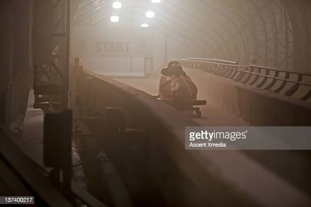 bobsled leaves start gate for descent along track - bobsleigh stock pictures, royalty-free photos & images