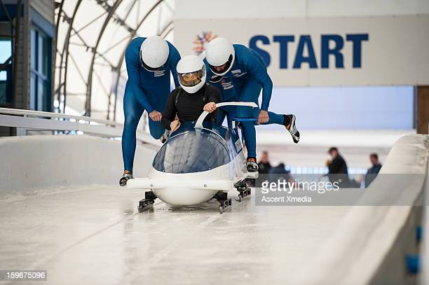 Bobsledders push bobsled out of start gate