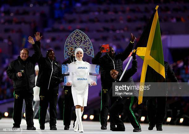 Bobsleigh racer Marvin Dixon of the Jamaica Olympic team carries his country's flag during the Opening Ceremony of the Sochi 2014 Winter Olympics at...