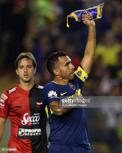 Boca Juniors' Carlos Tevez holds up the team standard after their Argentina First Division Superliga football match against Colon at La Bombonera...