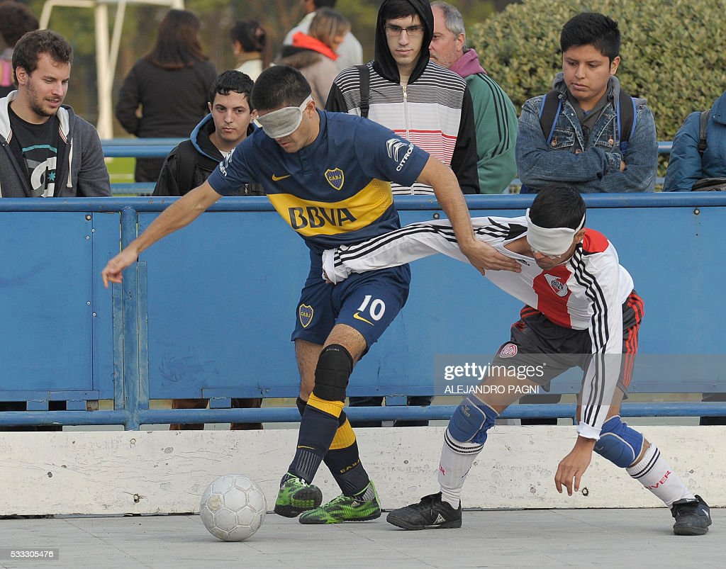 Boca Juniors' Claudio Monzon (L) vies for the ball with River Plate's Gustavo Maidana during a blind football match of the Argentine FaDeC (Argentine Federation of Sports for the Blind) championship in Buenos Aires on May 21, 2106. Boca Juniors won 1-0. Five-a-side blind football is contested by teams made up of four visually impaired outfield players wearing blindfolds with a goalkeeper who may be fully sighted. The football they play with contains ball bearings to produce a noise when it moves. / AFP / ALEJANDRO