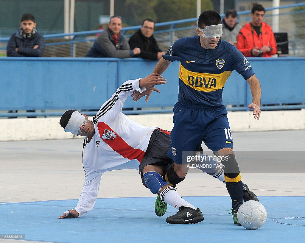 Boca Juniors' Claudio Monzon (R) vies for the ball with River Plate's Gustavo Maidana during a blind football match of the Argentine FaDeC (Argentine Federation of Sports for the Blind) championship in Buenos Aires on May 21, 2106. Boca Juniors won 1-0. Five-a-side blind football is contested by teams made up of four visually impaired outfield players wearing blindfolds with a goalkeeper who may be fully sighted. The football they play with contains ball bearings to produce a noise when it moves. / AFP / ALEJANDRO