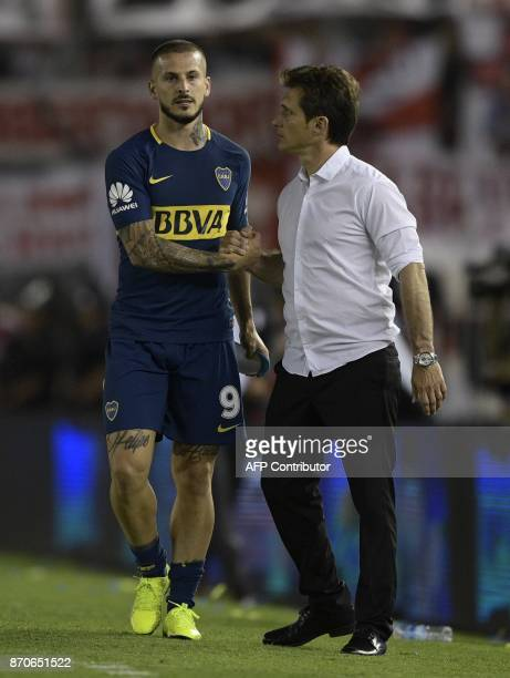 Boca Juniors' coach Guillermos Barros Schelotto greats to forward Dario Benedetto during the Argentine derby match against River Plate in the...