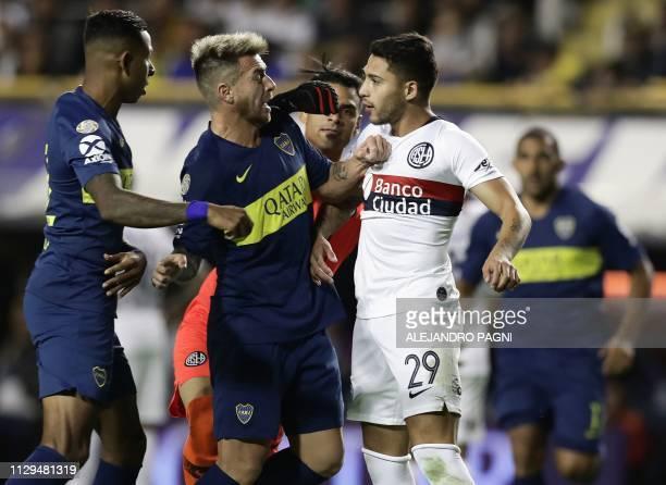 Boca Juniors' Colombian forward Sebastian Villa and defender Julio Buffarini argue with San Lorenzo's midfielder Victor Salazar during their...