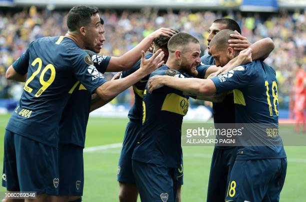 Boca Juniors' Dario Benedetto celebrates with Uruguayan teammate Nahitan Nandez and others after scoring the team's second goal against River Plate...