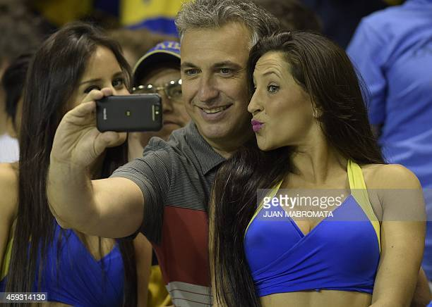 A Boca Juniors' fan takes a selfie next to a cheerleader before the start of the Copa Sudamericana 2014 semifinals first leg football match against...