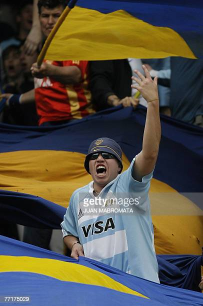 A Boca Juniors' fan wearing Los Pumas Argentinian National Rugby team jersey cheers his team during Argentina's first division football match against...
