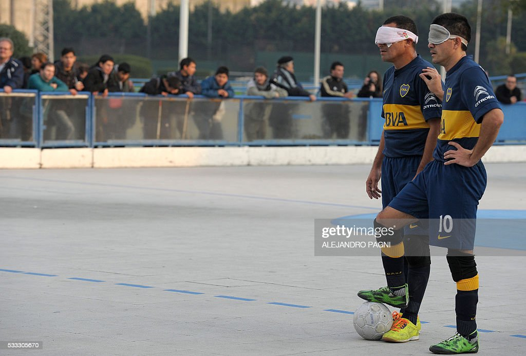 Boca Juniors' footballers Claudio Monzon (R) and Silvio Velo prepare to shoot a free kick against River Plate during a blind football match of the Argentine FaDeC (Argentine Federation of Sports for the Blind) championship in Buenos Aires on May 21, 2106. Boca Juniors won 1-0. Five-a-side blind football is contested by teams made up of four visually impaired outfield players wearing blindfolds with a goalkeeper who may be fully sighted. The football they play with contains ball bearings to produce a noise when it moves. / AFP / ALEJANDRO