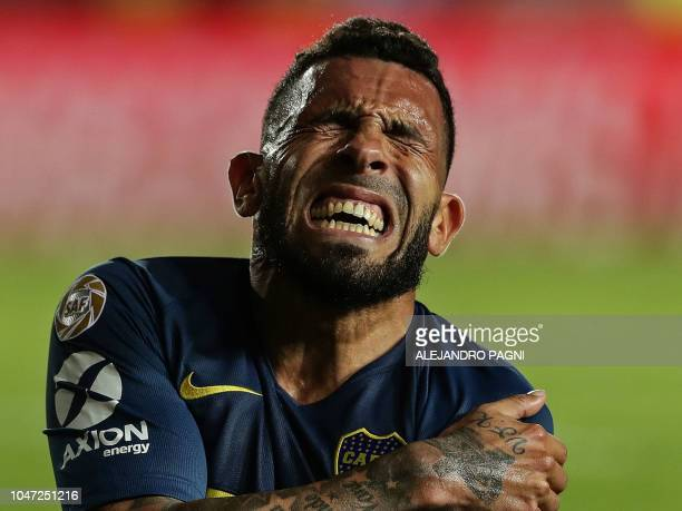 TOPSHOT Boca Juniors' forward Carlos Tevez gestures in pain during their Argentina First Division Superliga football match against Racing Club at...