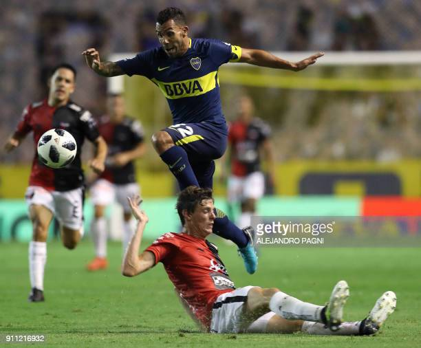Boca Juniors' forward Carlos Tevez jumps over Colon's defender German Conti and controls the ball during their Argentina First Division Superliga...