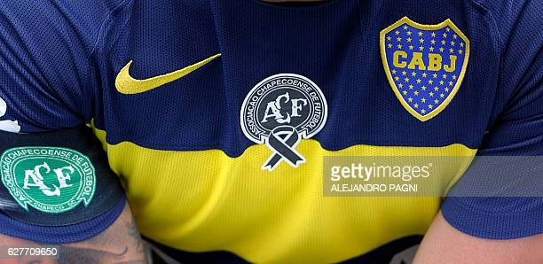 Boca Juniors forward Carlos Tevez poses wearing the Brazil's Chapecoense football team logo in his jersey to pay homage for the 71 victims of the...