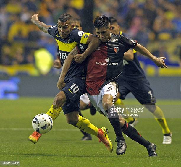 Boca Juniors' forward Carlos Tevez vies for the ball with Colon's defender Emanuel Olivera during their Argentina First Division football match at La...