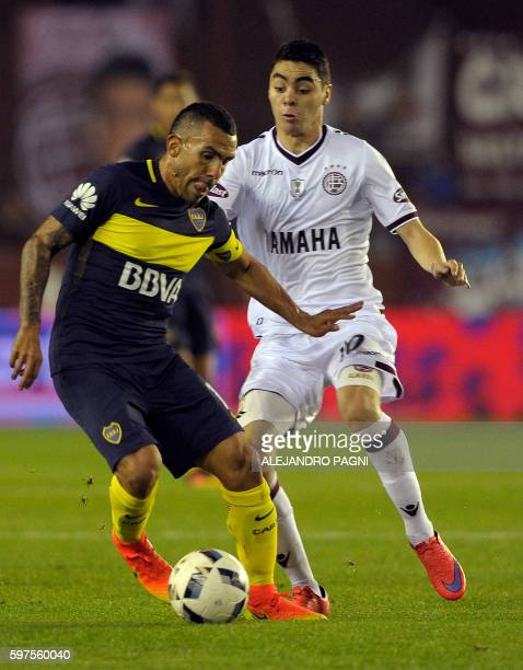 Boca Juniors' forward Carlos Tevez vies for the ball with Lanus' midfielder Miguel Almiron during their Argentina First Division football match at...