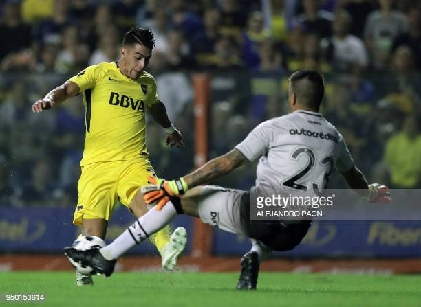 Boca Juniors' forward Cristian Pavon passes the ball to teammate forward Ramon Abila to score against Newell's Old Boys during their Argentina First...