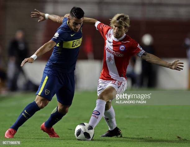 Boca Juniors' forward Cristian Pavon vies for the ball with Argentinos Juniors' midfielder Gaston Machin during their Argentina First Division...