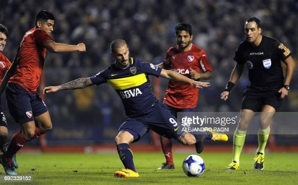 Boca Juniors' forward Dario Benedetto between Independiente's defender Alan Franco and midfielder Walter Erviti kicks to score the team's third goal...