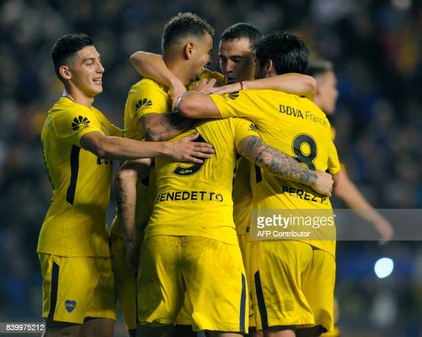 Boca Juniors' forward Dario Benedetto celebrates with teammates after scoring the team's third goal against Olimpo during their Argentina First...