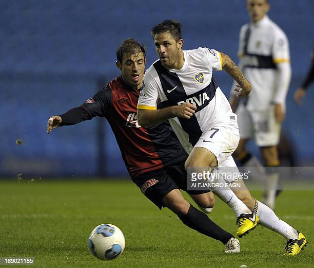 Boca Juniors' forward Juan Manuel Martinez controls the ball past Colon's midfielder Hernan Bernardello during their Argentine First Division...