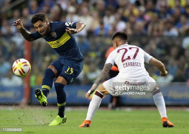Boca Juniors' forward Mauro Zarate kicks the ball next to Lanus' defender Gabriel Carrasco during their Argentina First Division Superliga football...