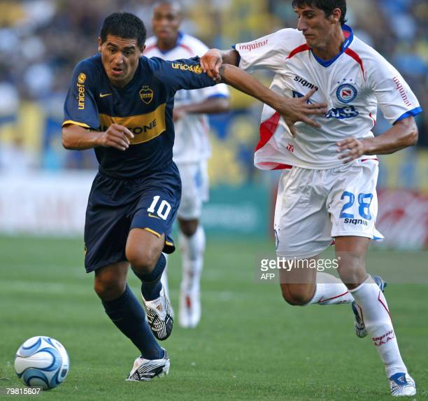 Boca Juniors' Juan Roman Riquelme vies for the ball with Gabriel Penalba of Argentinos Juniors during their Argentina first division football match...