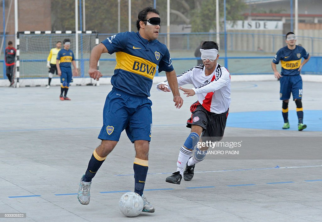 Boca Juniors' Luis Rodriguez (C) vies for the ball past River Plate's Gustavo Maidana during a blind football match of the Argentine FaDeC (Argentine Federation of Sports for the Blind) championship in Buenos Aires on May 21, 2106. Boca Juniors won 1-0. Five-a-side blind football is contested by teams made up of four visually impaired outfield players wearing blindfolds with a goalkeeper who may be fully sighted. The football they play with contains ball bearings to produce a noise when it moves. / AFP / ALEJANDRO