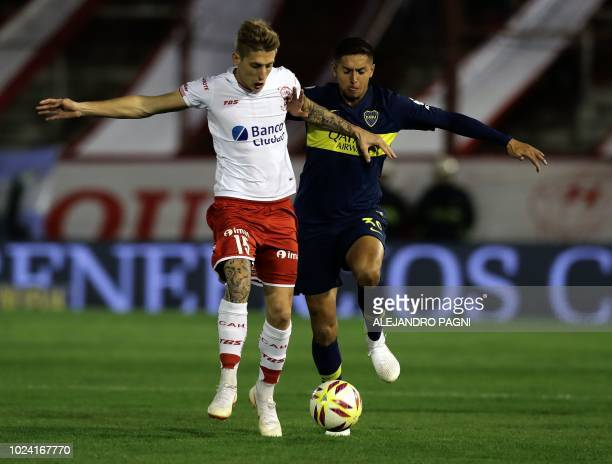 Boca Juniors' midfielder Agustin Almendra vies for the ball with Huracan's midfielder Ivan Rossi during an Argentina First Division Superliga...