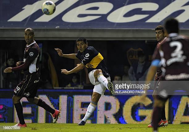 Boca Juniors' midfielder Juan Roman Riquelme kicks the ball next to Lanus' midfielder Guido Pizarro during their Argentine First Division football...