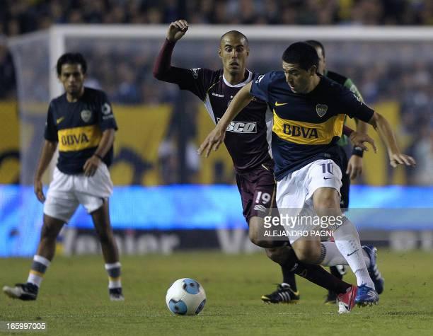 Boca Juniors' midfielder Juan Roman Riquelme vies for the ball with Lanus' midfielder Guido Pizarro during their Argentine First Division football...