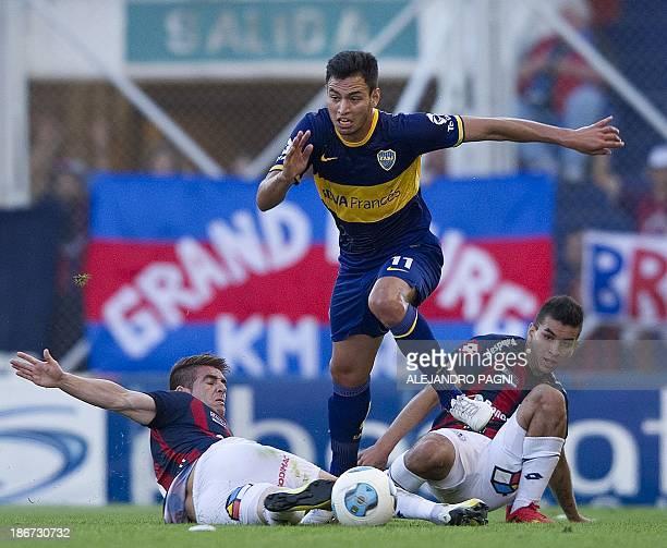 Boca Juniors' midfielder Juan Sanchez Mino controls the ball between San Lorenzo's midfielders Angel Correa and Julio Buffarini during their...
