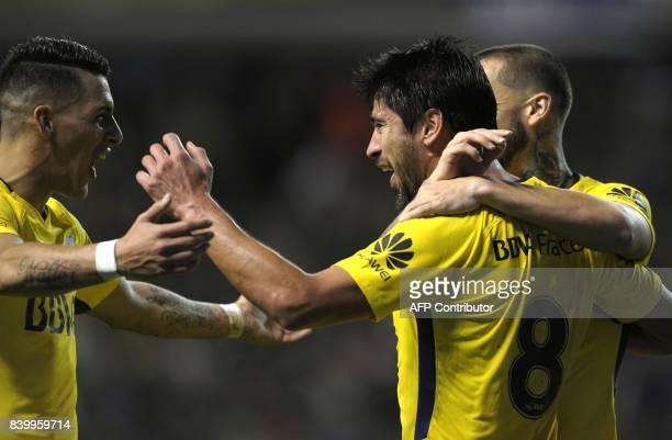 Boca Juniors' midfielder Pablo Perez celebrates with teammates forwards Cristian Pavon and Dario Benedetto after scoring the team's second goal...