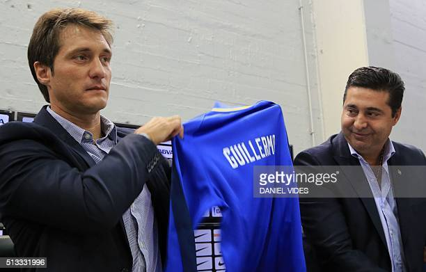 Boca Juniors new coach Guillermo Barros Schelotto holds a jersey with his name next to Boca Juniors' President Daniel Angelici during his...