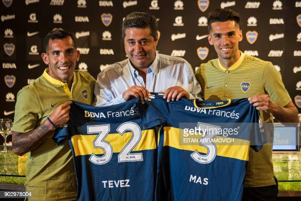 Boca Juniors' newly returned player Carlos Tevez and newly signed footballer Emmanuel Mas pose with their new jerseys next to Boca Juniors' President...