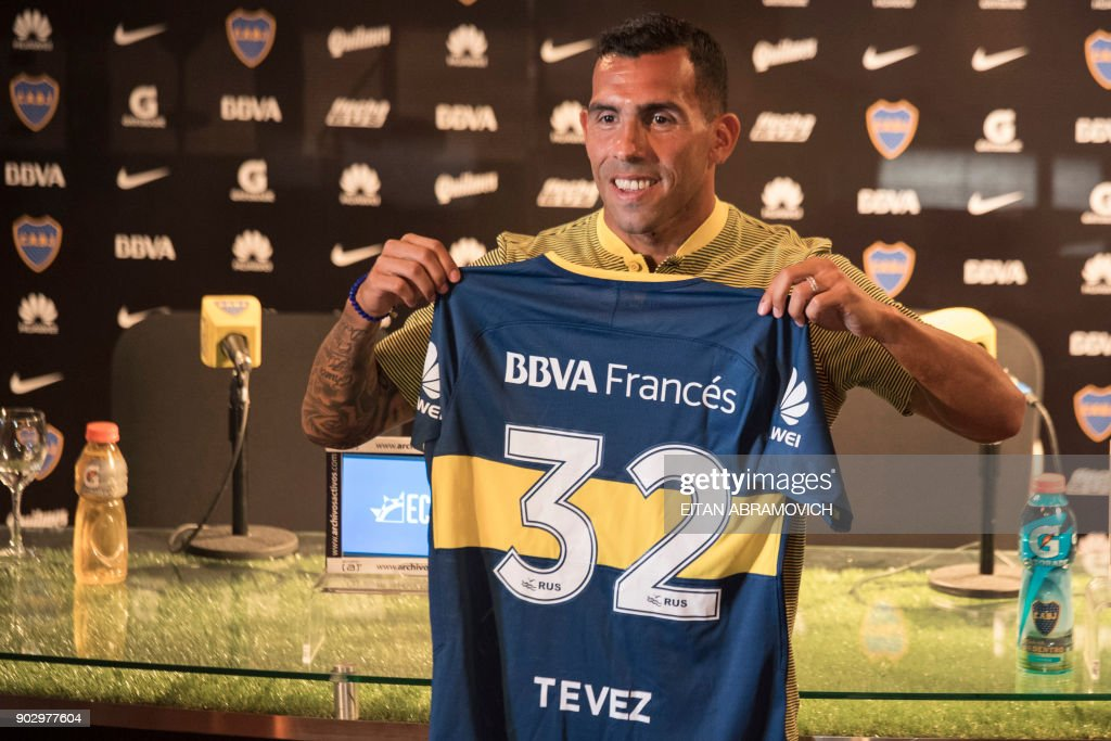 Boca Juniors' newly returned player Carlos Tevez poses with his new jersey during his official presentation at Los Cardales, Buenos Aires province, on January 09, 2018. Former Manchester United and Juventus striker Carlos Tevez agreed a move back to boyhood club Boca Juniors for the third time in his carreer. /