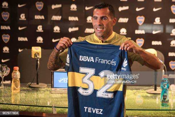 Boca Juniors' newly returned player Carlos Tevez poses with his new jersey during his official presentation at Los Cardales Buenos Aires province on...