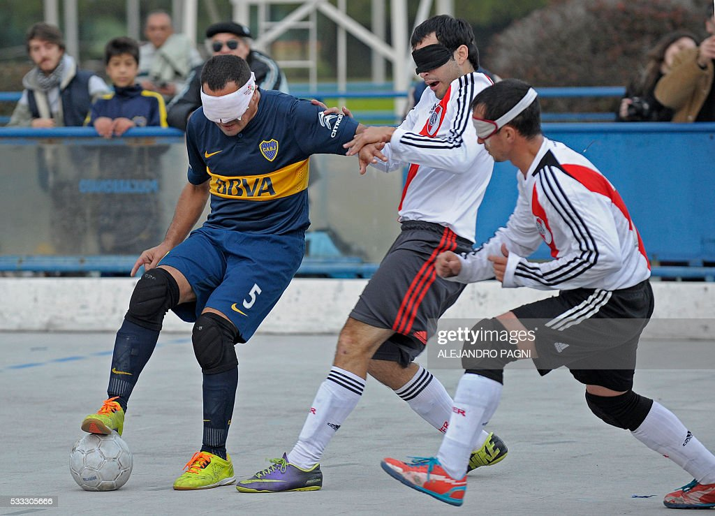 Boca Juniors' Silvio Velo (L) controls the ball past River Plate's footballers during a blind football match of the Argentine FaDeC (Argentine Federation of Sports for the Blind) championship in Buenos Aires on May 21, 2106. Boca Juniors won 1-0. Five-a-side blind football is contested by teams made up of four visually impaired outfield players wearing blindfolds with a goalkeeper who may be fully sighted. The football they play with contains ball bearings to produce a noise when it moves. / AFP / ALEJANDRO
