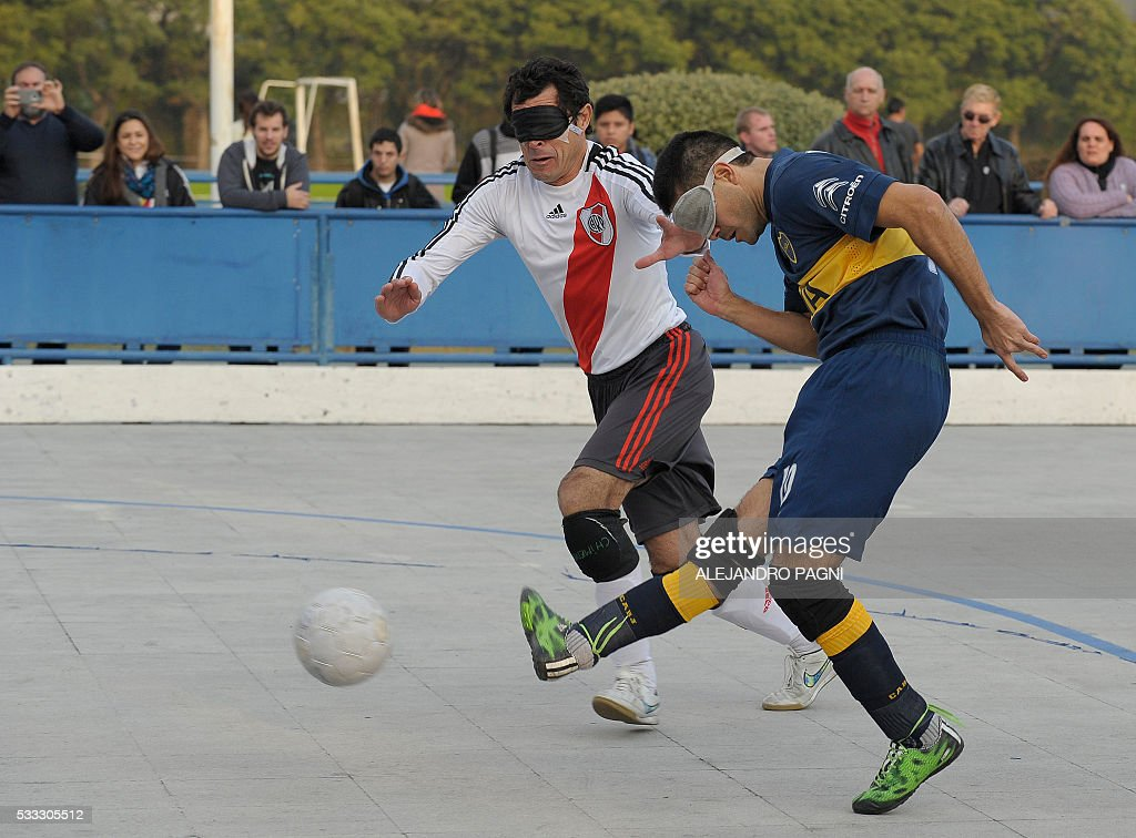 Boca Juniors' Silvio Velo (R) shoots the ball before River Plate's Oscar Mouzo during a blind football match of the Argentine FaDeC (Argentine Federation of Sports for the Blind) championship in Buenos Aires on May 21, 2106. Boca Juniors won 1-0. Five-a-side blind football is contested by teams made up of four visually impaired outfield players wearing blindfolds with a goalkeeper who may be fully sighted. The football they play with contains ball bearings to produce a noise when it moves. / AFP / ALEJANDRO