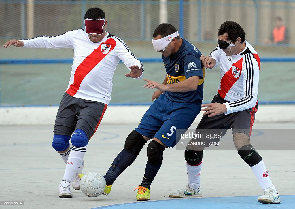 Boca Juniors' Silvio Velo (C) vies for the ball with River Plate's Daniel Vega (L) and Oscar Mouzo during a blind football match of the Argentine FaDeC (Argentine Federation of Sports for the Blind) championship in Buenos Aires on May 21, 2106. Boca Juniors won 1-0. Five-a-side blind football is contested by teams made up of four visually impaired outfield players wearing blindfolds with a goalkeeper who may be fully sighted. The football they play with contains ball bearings to produce a noise when it moves. / AFP / ALEJANDRO