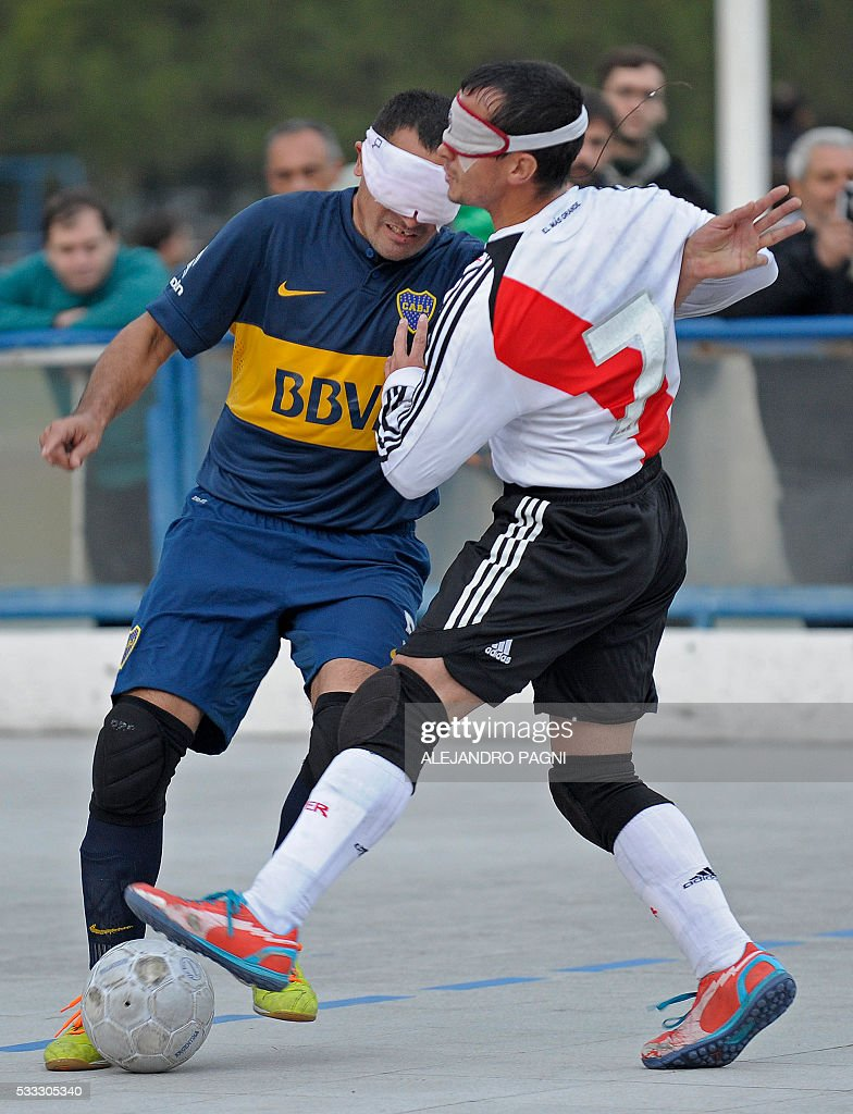 Boca Juniors' Silvio Velo (L) vies for the ball with River Plate's Marcelo Panisa during a blind football match of the Argentine FaDeC (Argentine Federation of Sports for the Blind) championship in Buenos Aires on May 21, 2106. Boca Juniors won 1-0. Five-a-side blind football is contested by teams made up of four visually impaired outfield players wearing blindfolds with a goalkeeper who may be fully sighted. The football they play with contains ball bearings to produce a noise when it moves. / AFP / ALEJANDRO