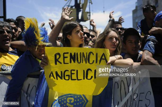 A Boca Juniors' supporter holds a sign demanding the resignation of the team's president Daniel Angelici as they wait for their team players outside...