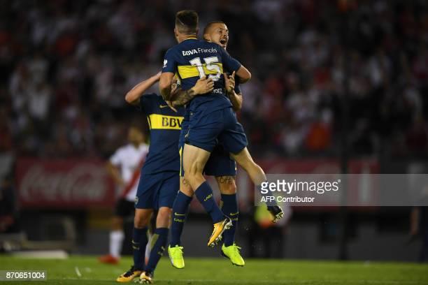 Boca Juniors' Uruguayan midfielder Nahitan Nandez celebrates with teammate forward Dario Benedetto during the Argentine derby match against River...