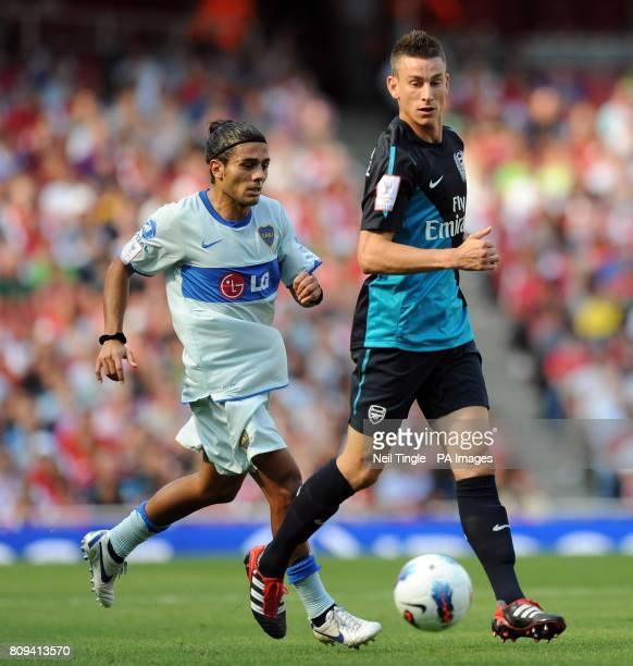 Boca Juniors Walter Erviti and Arsenal's Laurent Koscielny battle for the ball during the Emirates Cup match at the Emirates Stadium London