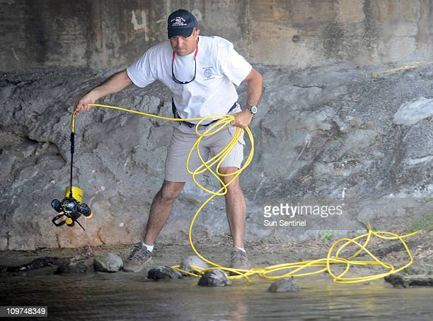 A Boca Raton police dive team member launches a remote controlled underwater camera during a search of the C15 canal under the Congress Avenue Bridge...