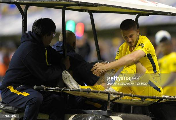 Boca's forward Dario Benedetto leaves the field after being injured during the Superliga first division tournament match against Racing Club at La...
